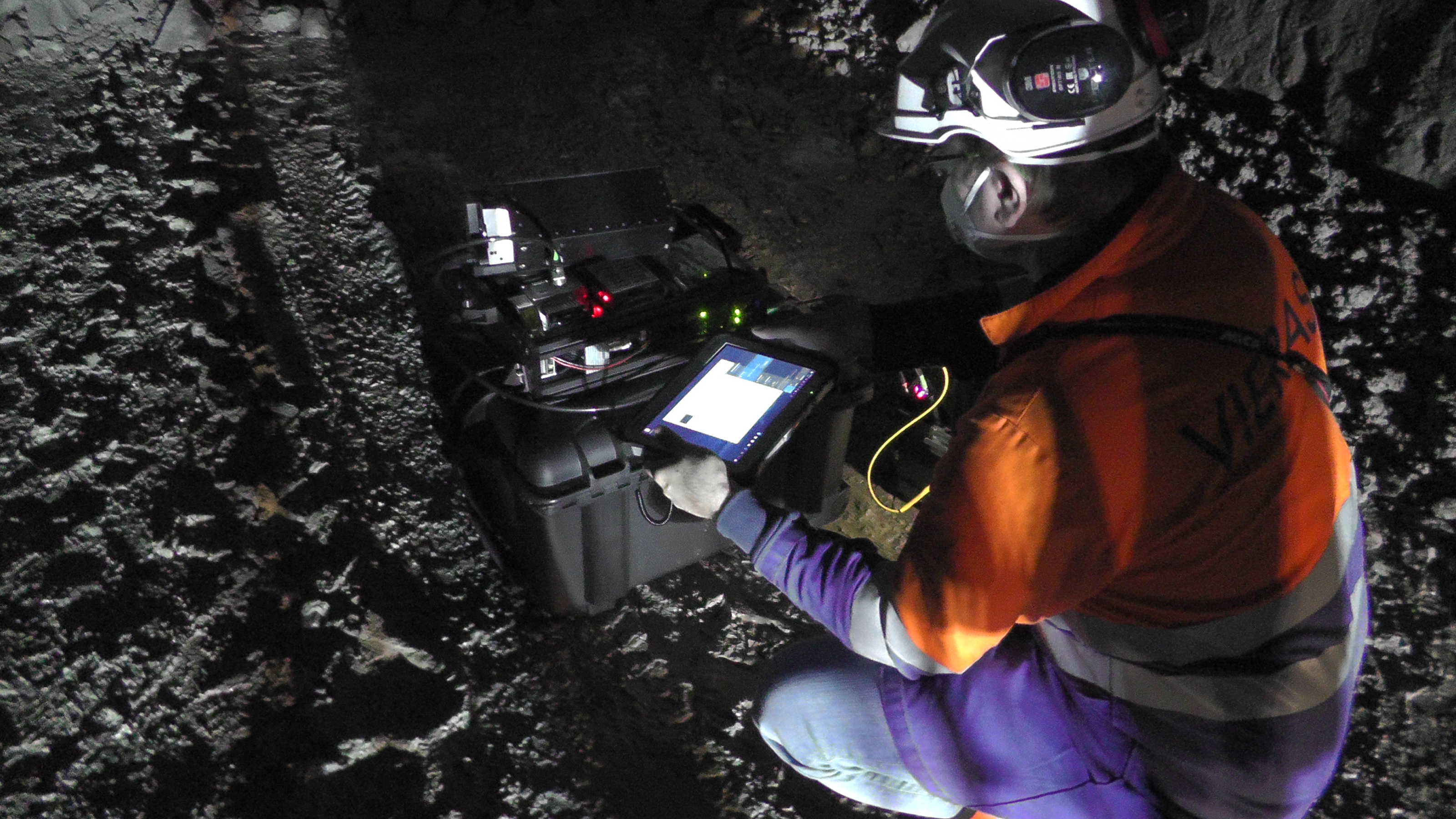 A worker measures ore content in a dark mine.