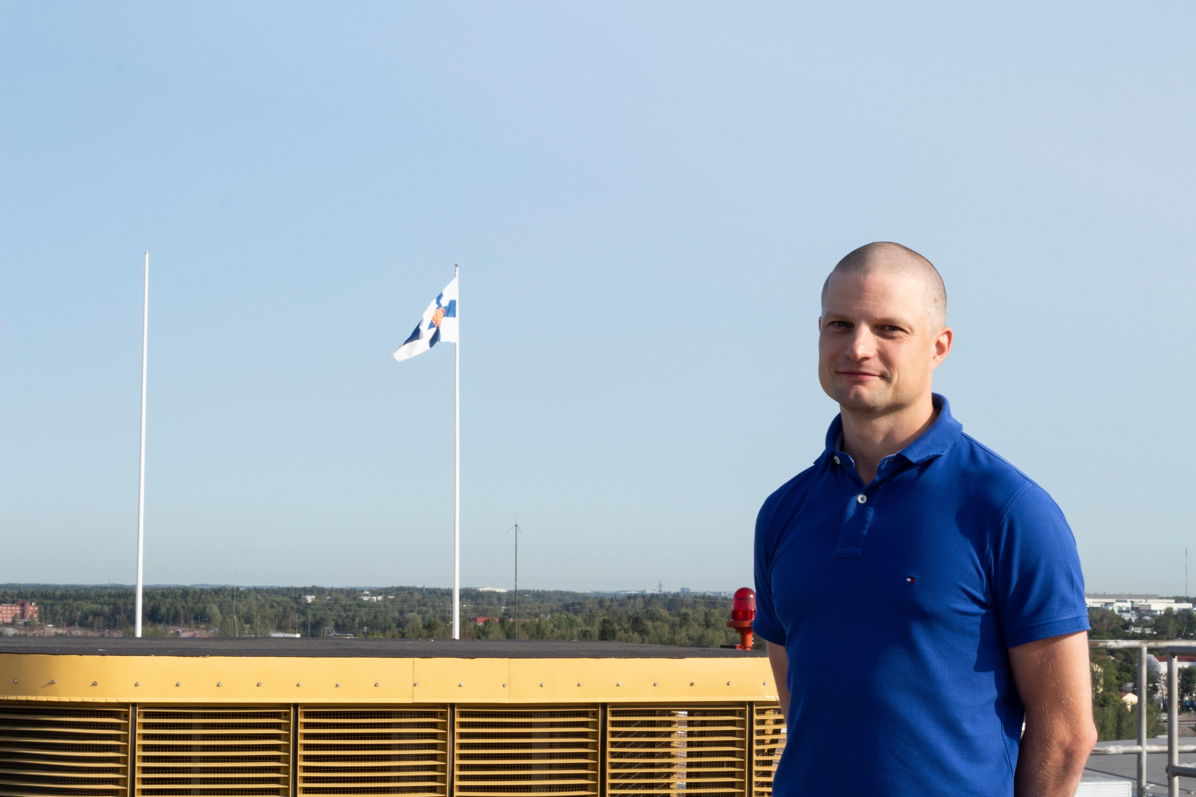 Projektipäällikkö Juha Kareinen hymyilee ulkona aurinkoisessa säässä.