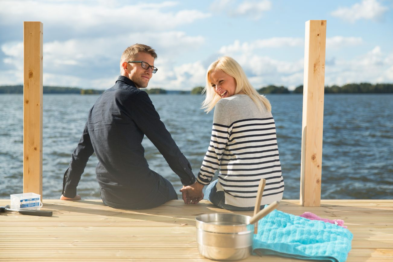 Man and woman sitting on a pier by the lake.