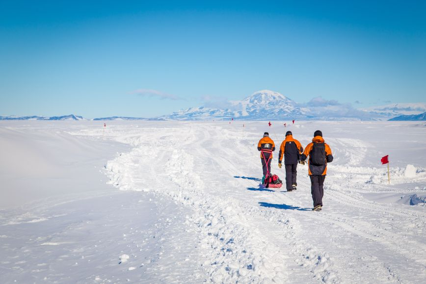 Three people walking in Antarctica.