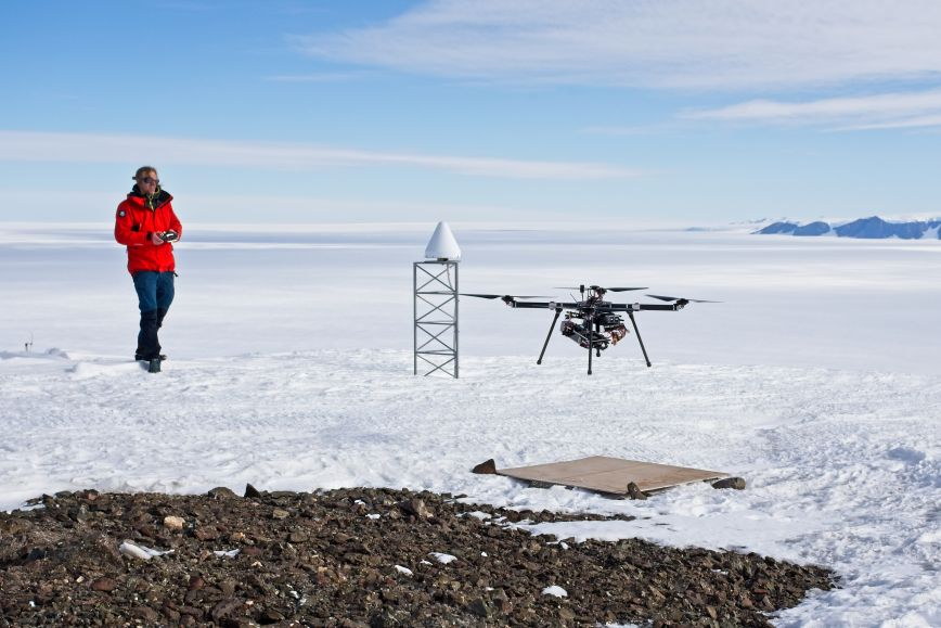 Researcher Arttu Raja-Halli operating a drone in a sunny and snowy view.